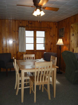 Dining table sits directly adjacent to the living room.  The living room, with big picture windows, faces the lake.  Great location!