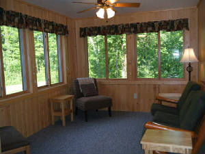 The sunroom is located at the South end of the cabin (opposite end of the main living room).  It is furnished with a couch and living room chairs.  Full of windows - you will see deer outside if you are awake early enough in the morning!