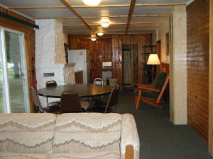 "Cabin 1 ""great room"" flows from Living Area to Dining to Kitchen.  The large dining table is located next to the lakeside sliding patio door.  And the living room is full of picture windows.   What a view!"