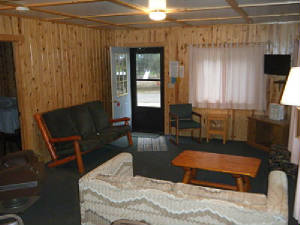 Cabin 1 Living Room includes a log couch, a hide-a-bed couch, living room chairs and an antique chair that started its life onboard a train!  High Definition TV with DVD player in the NorthWest Corner