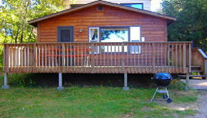 Condo #12 entry with spacious deck.  The deck area has a direct view of the lake.  All of our cabins include their own Picnic Table and BBQ grill.